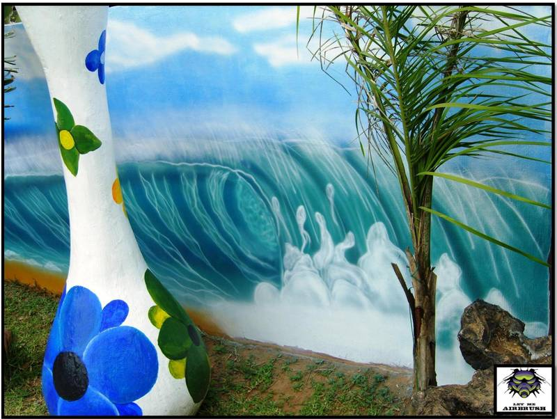A nature scene painted on a wall behind a pool.  Gives a whole different atmosphere to this outside play area!